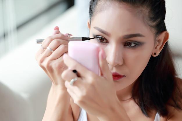흰색 조끼와 블루 진 아름다움과 젊은 섹시 아시아 여자 게시 메이크업의 초상화
