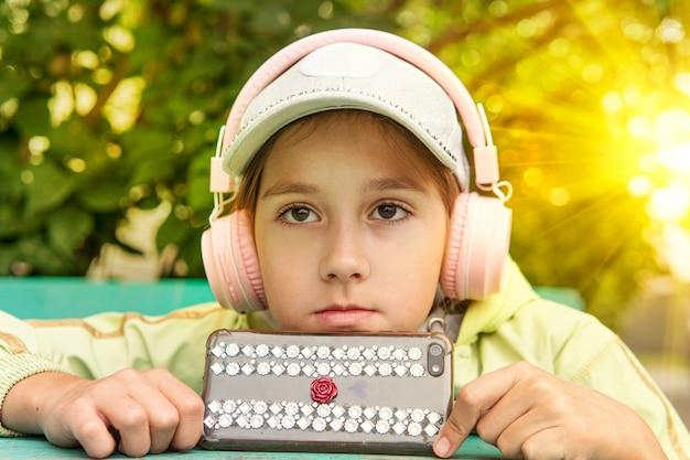 긴 갈색 머리에 흰색 모자를 쓰고 밖에서 음악을 들으며 헤드폰을 끼고 있는 미인 소녀의 초상화. 아이는 전화로 오디오북을 듣습니다. 어학연수.