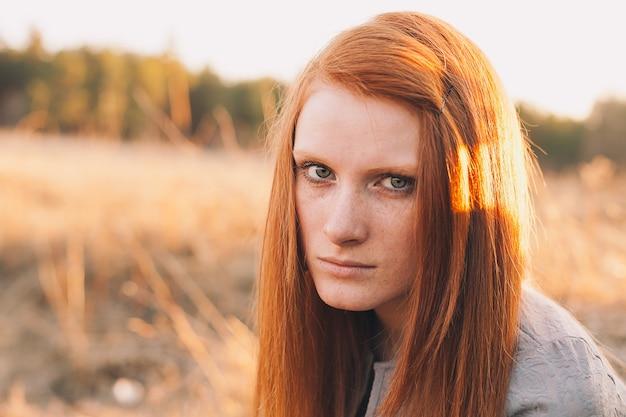 フィールド上の自然の背景に赤い髪の美しさの10代のモデルの女の子の肖像画