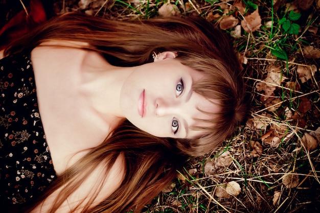 自然を背景に赤い髪の美しさの10代のモデルの女の子の肖像画。温かみのある色調