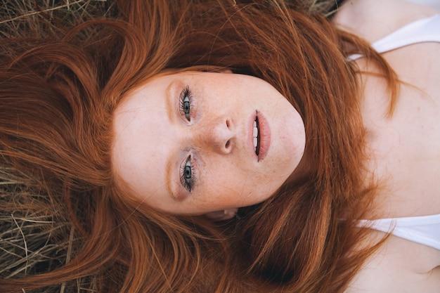 自然を背景に赤い髪の美しさの10代のモデルの女の子の肖像画