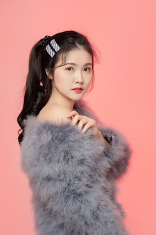 アジアの美しさの女性の肖像画と白い肌にピンクのカメラを見てもらいます。