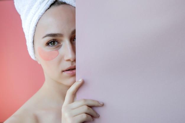 ピンクの背景に眼帯を持つ美女の肖像画。目の下のマスクと女性の美しさの顔。スキンケア、コピースペースのある化粧品コンセプト。
