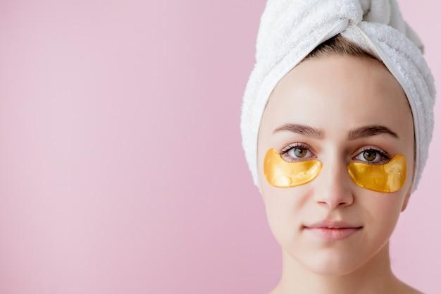 ピンクの背景にアイパッチを持つ美容女性の肖像画。目の下のマスクを持つ女性美容顔。
