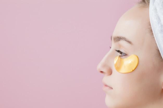 ピンクの背景に眼帯を持つ美容女性の肖像画