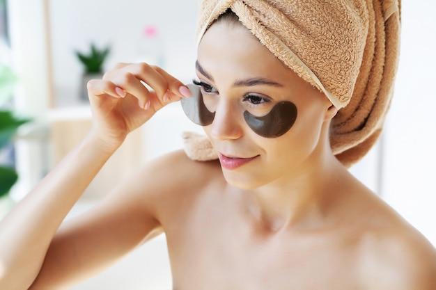 Портрет женщины красоты с повязками на глазах, показывающими эффект идеальной кожи.