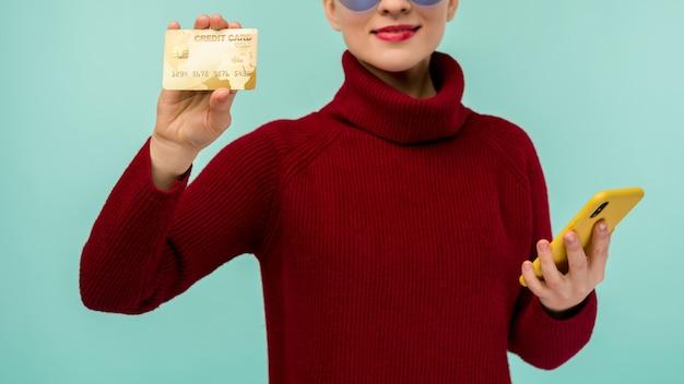 파란색 배경 위에 절연 휴대 전화를 들고있는 동안 플라스틱 신용 카드를 보여주는 뷰티 젊은 여자의 초상화