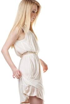 Портрет красивой танцующей блондинки с длинными волосами на белом фоне