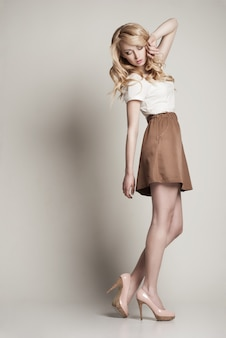 Портрет красивой позирующей блондинки с длинными вьющимися волосами на белом фоне