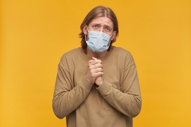Портрет мужчины попрошайничества со светлыми волосами и бородой. носить бежевый свитер, медицинскую защитную маску. спрашивает, сложив ладони, наклоняет голову. изолированные над желтой стеной