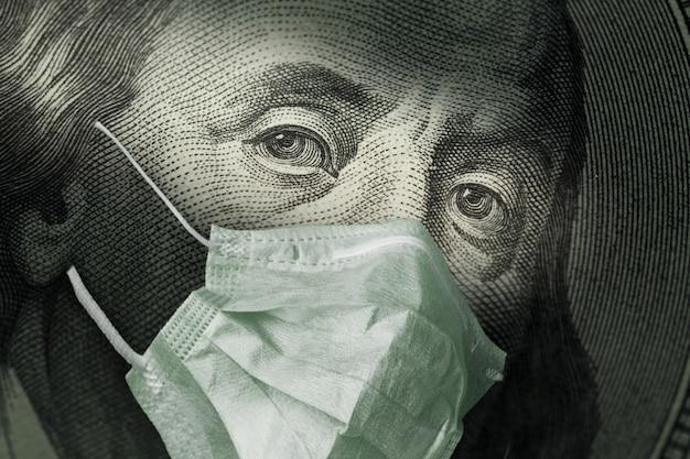 コロナウイルスcovid-19の医療用マスクが付いたベンジャミンフランクリン100ドル紙幣の肖像画。