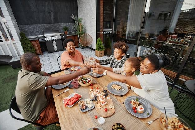 야외에서 함께 저녁 식사를 즐기면서 안경을 부딪치는 큰 아프리카계 미국인 가족의 초상화와 ...