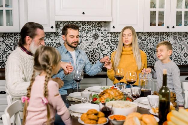 큰 가족의 초상화 축제 테이블에 앉아기도하면서 서로 손을 잡고