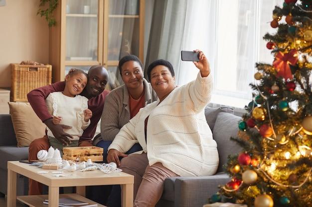 一緒に家でクリスマスを楽しみながら自分撮り写真を撮る大きな幸せなアフリカ系アメリカ人家族の肖像画