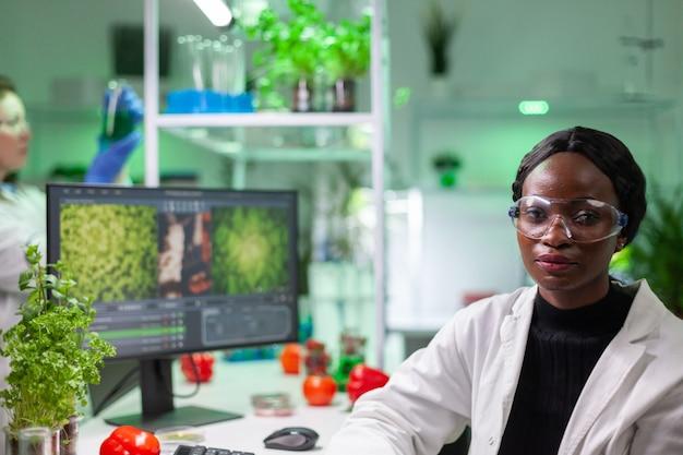 微生物学研究室に立っている間カメラを覗き込んでいる白いコートを着た生物学者研究者の女性の肖像画