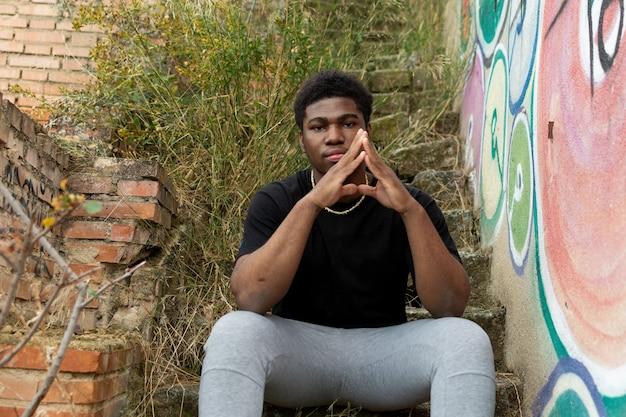버려진 된 계단에 앉아 흑인 소년의 초상화.