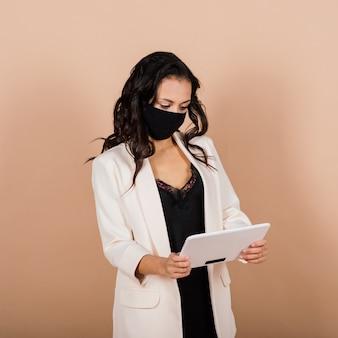 Портрет черной коммерсантки в маске во время вирусной эпидемии в студии.