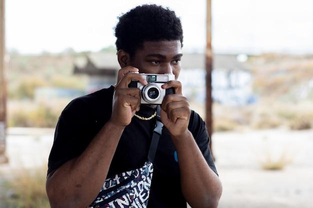 빈티지 카메라로 사진을 찍는 흑인 남자의 초상화.