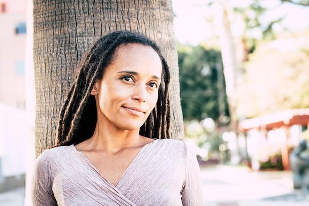 街や通りを背景に公園で黒人の若い女性の肖像画