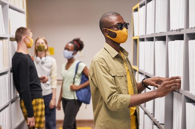 図書館で本を選択しながらマスクを身に着けている盲目のアフリカ系アメリカ人男性の肖像画