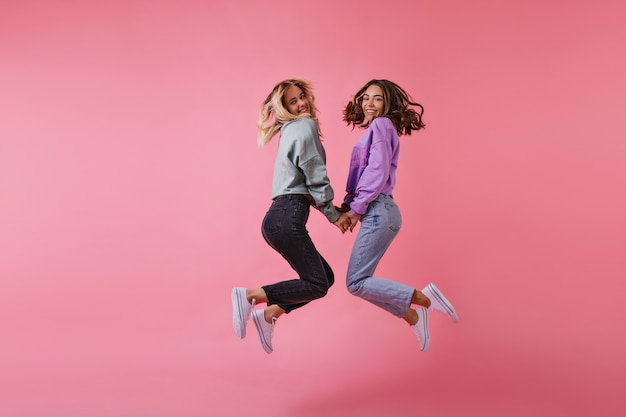 Портрет веселых лучших друзей, держащихся за руки на розовом. очаровательные сестры в модных штанах прыгают и смеются.