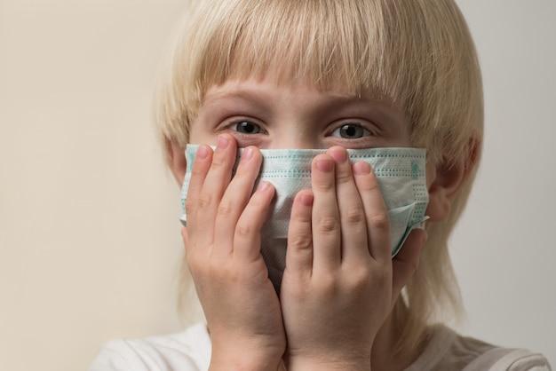 医療マスクで金髪の少年の肖像画。子供はインフルエンザウイルスのマスクで顔を覆った。