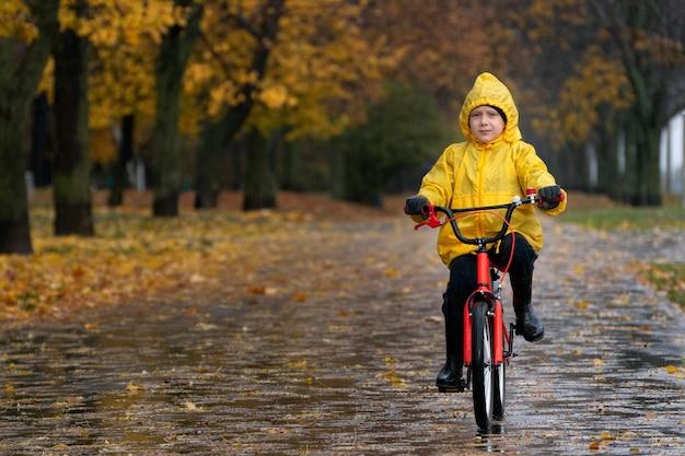 Портрет белокурого мальчика в желтом плаще. мальчик едет на велосипеде в осеннем парке под дождем. велосипедная прогулка по городу.