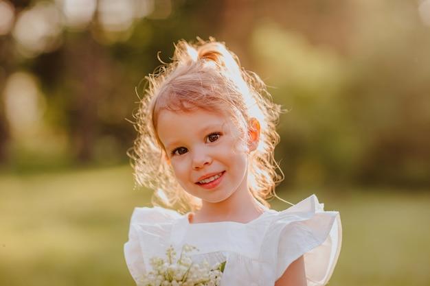 公園で花束を持っているブロンドの女の子の肖像画。コピースペース。