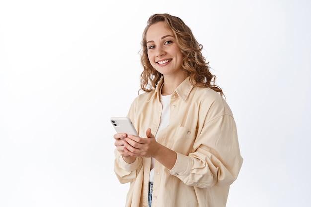 휴대폰을 사용하고 앞에서 기쁘게 웃고 있는 금발 소녀의 초상화, 휴대폰으로 채팅, 흰 벽에 기대어 서 있는