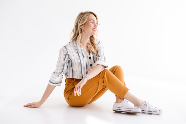 제쳐두고 찾고 흰색 벽 위에 절연 바닥에 앉아 안경을 쓰고 금발 웃는 여자의 초상화