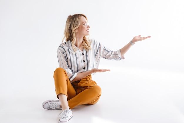 흰색 벽 위에 절연 바닥에 앉아있는 동안 가리키는 copyspace를보고 안경을 쓰고 금발 웃는 여자의 초상화