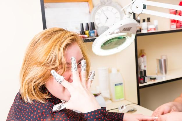 스파에서 젤 매니큐어를 하는 동안 호일 랩에 손톱을 감싼 채로 얼굴 앞에서 손을 잡고 스파에서 금발 여성의 초상화