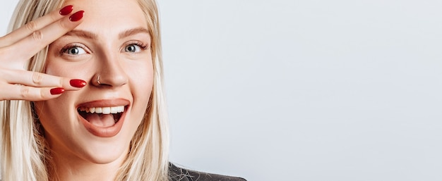 Портрет блондинки, радостно подмигивающей, показывая жест победы мира, как дурачиться, будучи оптимистом