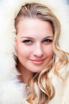 冬の背景に毛皮のコートで金髪の若い女性の肖像画