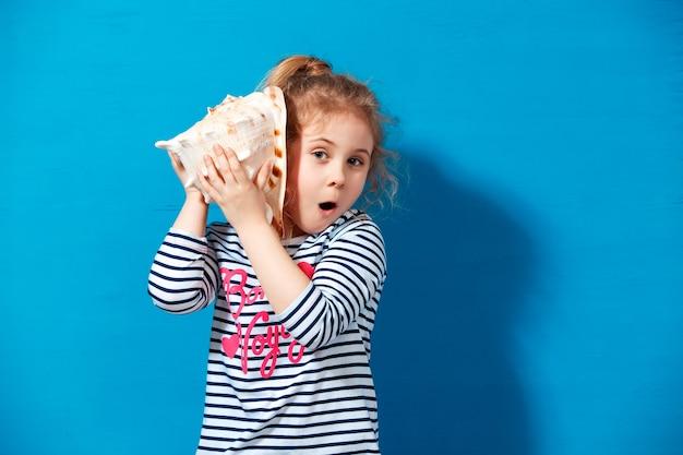 金髪の子供の女の子の肖像画は青い壁で貝殻を聞きます。夏休みのコンセプト。