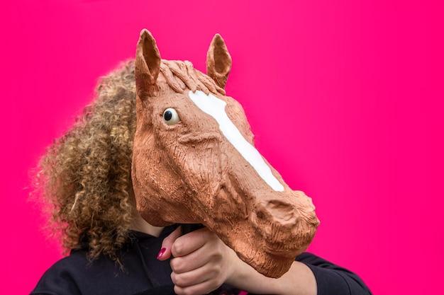 明るいピンクの馬の頭のおもちゃを保持している金髪の巻き毛の少女の肖像画。