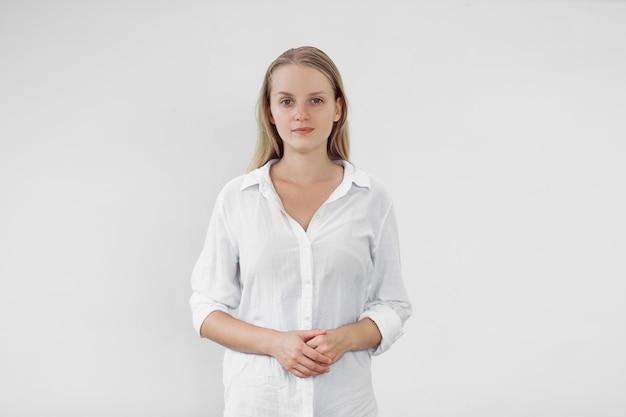 Портрет блондинки в белой рубашке на белой стене