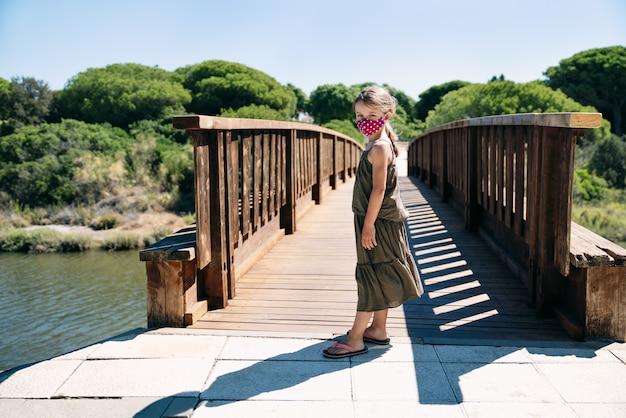 コロナウイルスのパンデミックの真っ只中に緑のドレスを着た真面目な顔を持つ松の木と木製の橋で休暇中にフェイスマスクと青い目をしたブロンドの女の子の肖像画