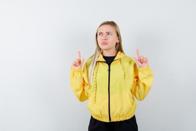 Tracksuit에서 가리키는 잠겨있는 전면보기를 찾고 금발 아가씨의 초상화