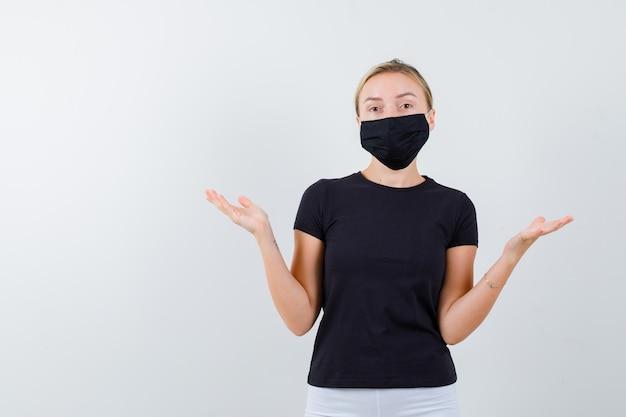 고립 된 검은 티셔츠에 무기력 한 제스처를 보여주는 금발 아가씨의 초상