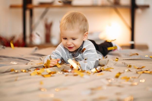 회색 스웨터와 검은 색 청바지에 금발 작은 소년의 초상화 색종이 가운데 침대에 누워 정면을보고