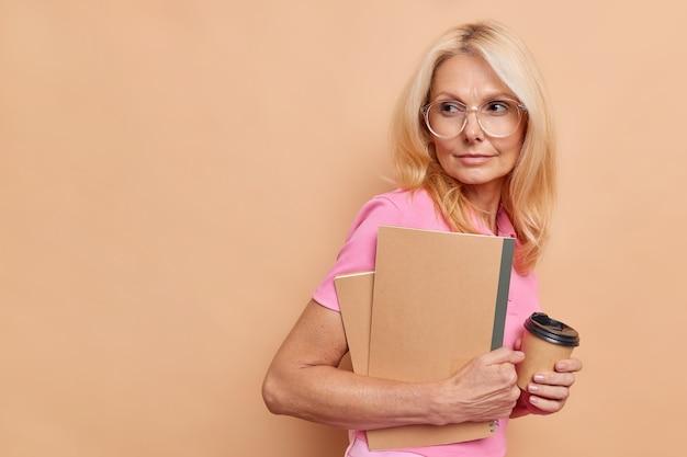 금발 중년 여성의 초상화는 사려 깊은 표정으로 메모장에 체크리스트를 작성하고 갈색 벽 복사 공간에 격리된 향기로운 테이크아웃 커피를 마신다