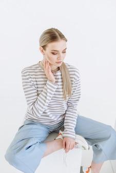 Портрет блондинки модельной женщины, сидящей на белой сцене в циклораме