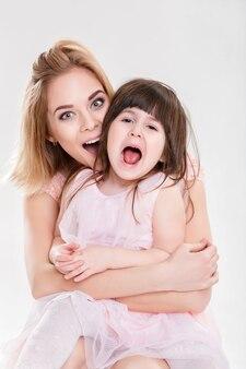 금발 엄마와 핑크 드레스 공주 포옹과 회색 배경에 웃 고 달콤한 작은 딸의 초상화. 가족