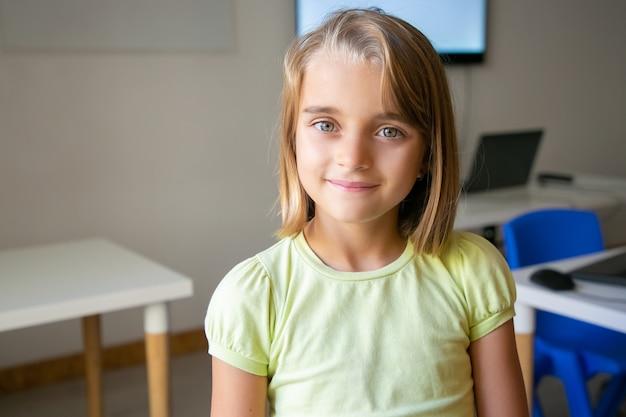 黄色のシャツを着た金髪のかわいい女の子の肖像画