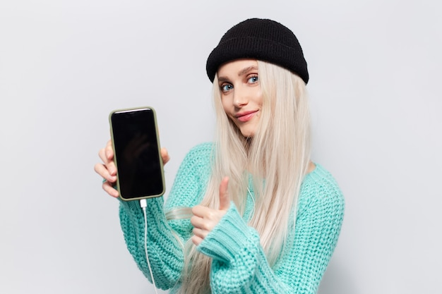 スマートフォンと白い背景の上の親指を示す金髪のかわいい女の子の肖像画