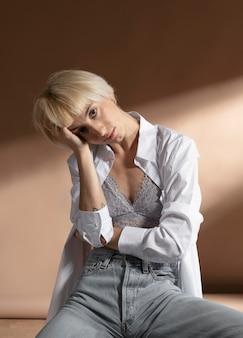 白いシャツを着てポーズをとってブラを見せている金髪の短い髪の女性の肖像画