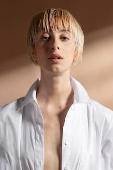 白いシャツでポーズをとって金髪の短い髪の女性の肖像画