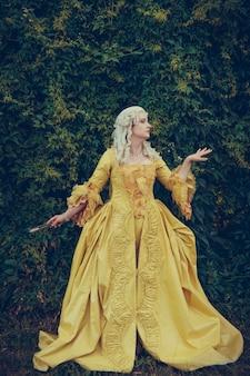 Портрет блондинки, одетой в историческую одежду в стиле барокко со старой модной прической, на открытом воздухе. роскошное средневековое платье