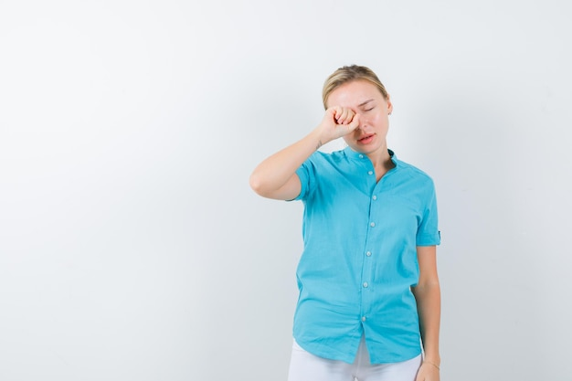 Портрет блондинки, протирающей глаз, плача в синей блузке, изолированные